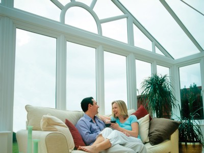 Gable end conservatory viewed from inside with couple on settee